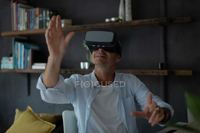 Vista frontale di uomo maturo caucasico utilizzando cuffie realtà virtuale in soggiorno a casa — Foto stock