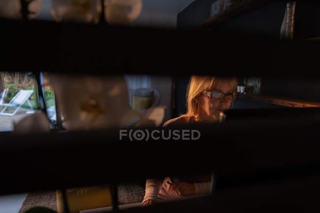 Vue de face de femme blanche mature utilisant un ordinateur dans le salon à la maison — Photo de stock