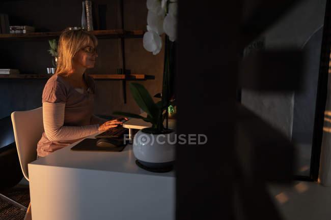 Vue latérale de femme blanche mature utilisant l'ordinateur dans le salon à la maison le soir — Photo de stock