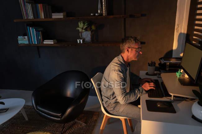Vue latérale de l'homme caucasien mature utilisant l'ordinateur dans le salon à la maison le soir — Photo de stock