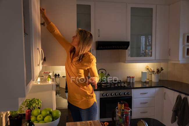 Side view of mature Caucasian woman opening the door of cupboard in kitchen at home — Stock Photo