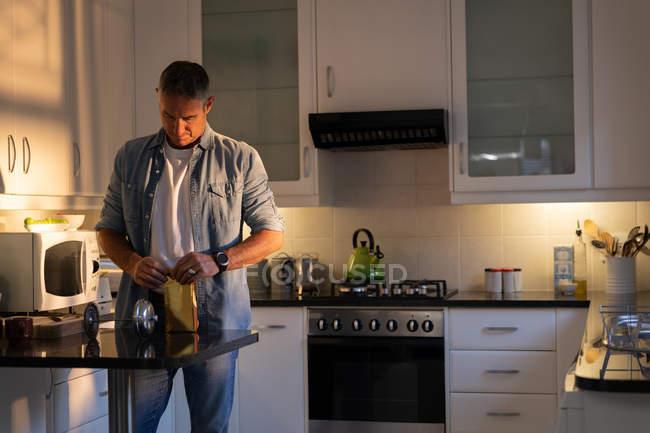 Vorderansicht eines reifen kaukasischen Mannes, der bei Sonnenaufgang zu Hause in der Küche steht und konzentriert eine Papiertüte Kaffee öffnet — Stockfoto