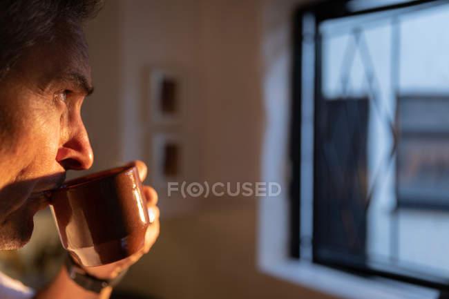 Вид збоку вдумливого зрілого Кавказького чоловіка з кавою і переглядаючи вікно в кухні будинку на світанку — стокове фото