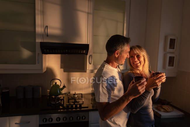 Вид збоку щасливого зрілої кавказької пари з кавою в той час як вони дивляться один на одного в кухні будинку на світанку — стокове фото