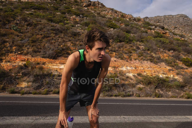 Front view of exhausted young Caucasian man standing with water bottle on road — Stock Photo