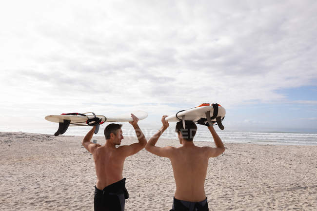 Rear view of Caucasian father and son standing with surfboard at beach — Photo de stock