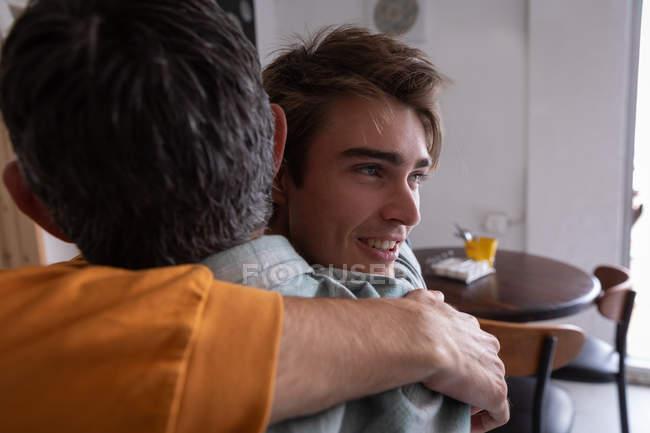 Крупный план Кавказского отца и сына, обнимающих друг друга дома — стоковое фото