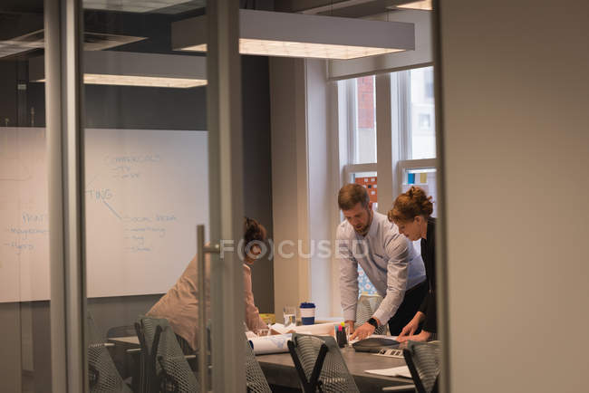 Side view of diverse business people discussing with each other in a meeting at office — Stock Photo