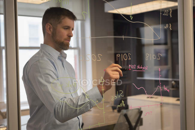 Front view of Caucasian businessman writing on glass wall at office — Stock Photo