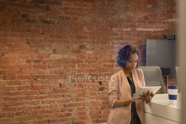 Вигляд з передньої частини афроамериканців ділового використання цифрової таблетки проти цегляної стіни в офісі — стокове фото