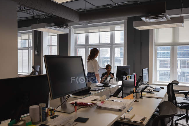 Side view of diverse female business executives interacting with each other in office — Stock Photo