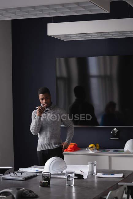 Vista frontale dell'uomo d'affari afroamericano che parla al cellulare in sala conferenze in ufficio — Foto stock