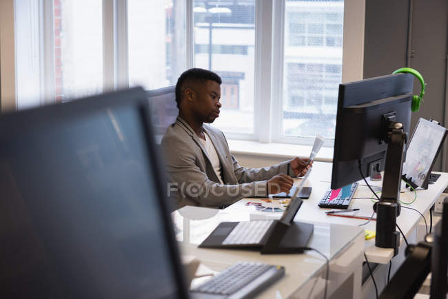 Side view of African-american businessman looking at graphic chart in office — Stock Photo