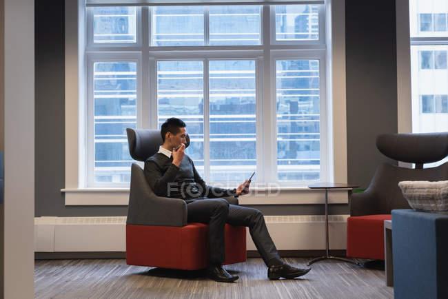 Вид сбоку на азиатского бизнесмена, использующего цифровой планшет во время разговора по мобильному телефону в офисе — стоковое фото