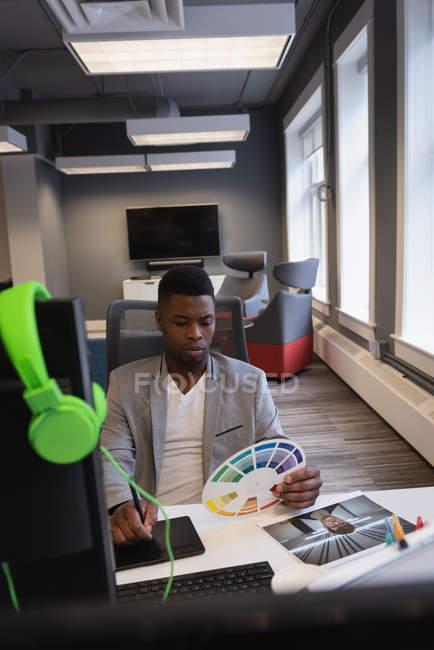 Vista frontale dello stilista afroamericano maschile utilizzando tablet grafico mentre si guarda campione di colore — Foto stock