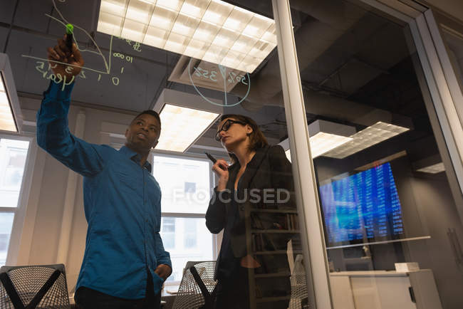 Low angle view of African-american businessman showing growth chart to his Caucasian colleague on glass wall at office — Stock Photo