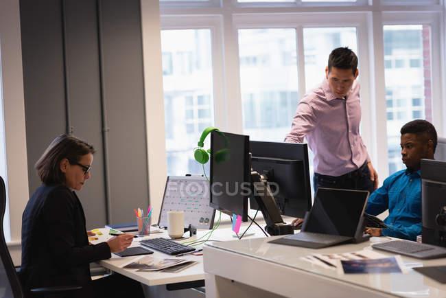 Vista frontal de Diversos empresarios trabajando juntos en la oficina - foto de stock