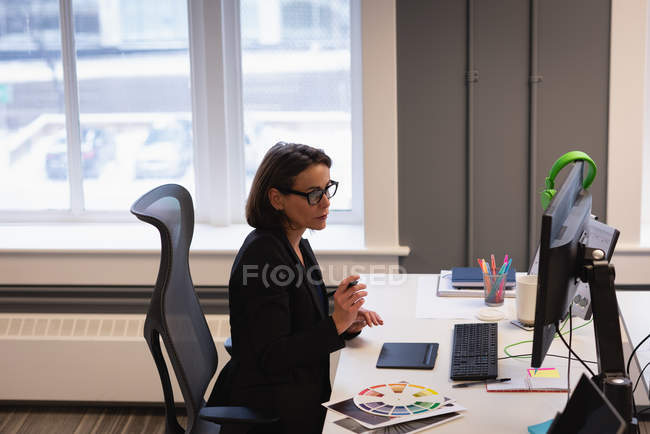 Side view of Caucasian female fashion designer working at desk in office — Stock Photo