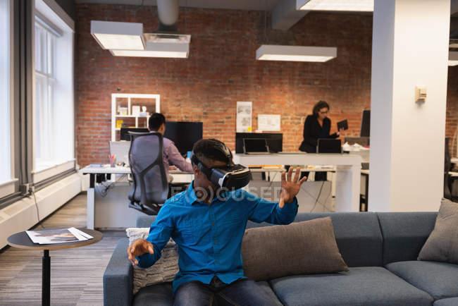 Vista frontale dell'uomo d'affari afro-americano che utilizza cuffie di realtà virtuale mentre i colleghi lavorano in background in ufficio — Foto stock