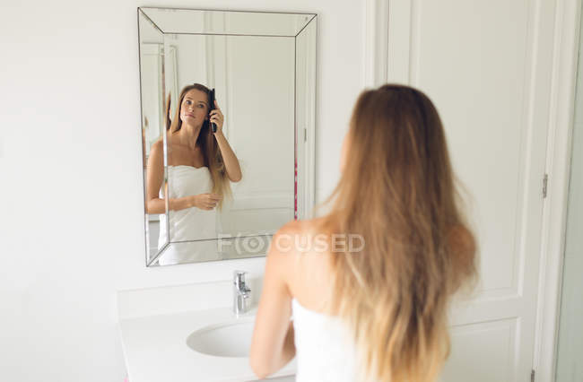 Mirror image of beautiful woman comb her hair in bathroom at home — Stock Photo
