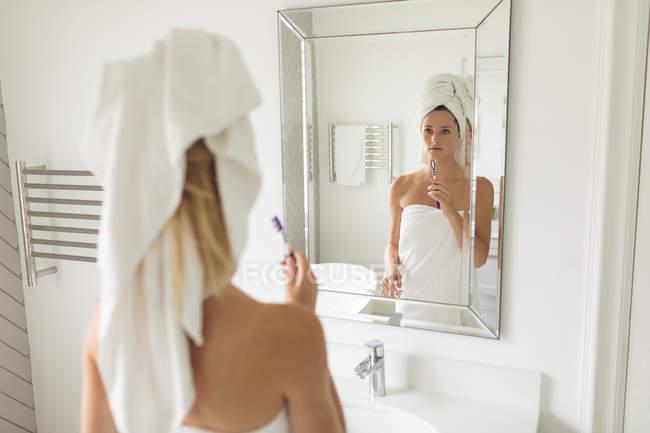 Mulher bonita pensativa que está na frente do espelho ao prender o toothbrush — Fotografia de Stock