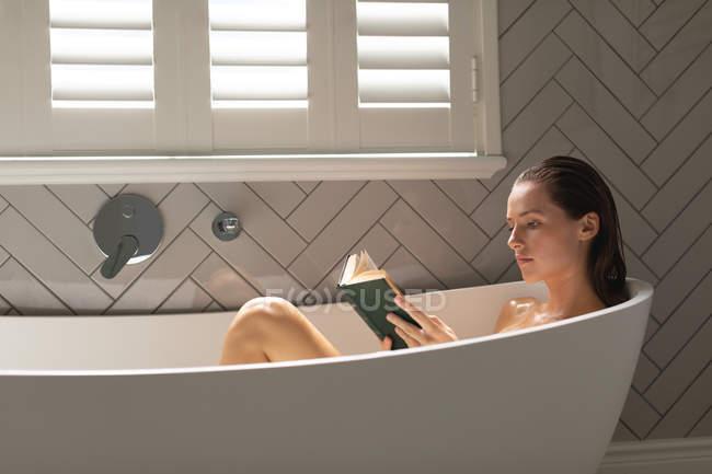Женщина читала книгу в ванне в ванной — стоковое фото
