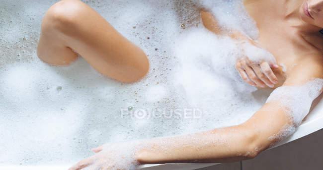 Mulher tomando banho na banheira no banheiro — Fotografia de Stock