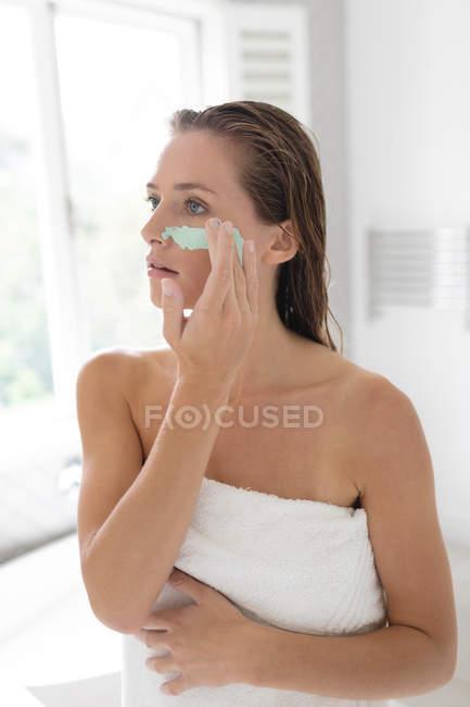 Nahaufnahme einer Frau, die nach einem Bad eine Gesichtsmaske aufträgt — Stockfoto
