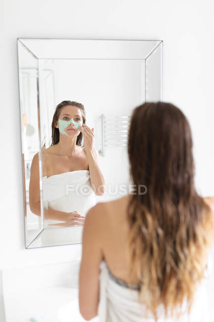 Rückansicht einer Frau, die nach dem Bad in den Spiegel schaut und eine Gesichtsmaske aufträgt — Stockfoto