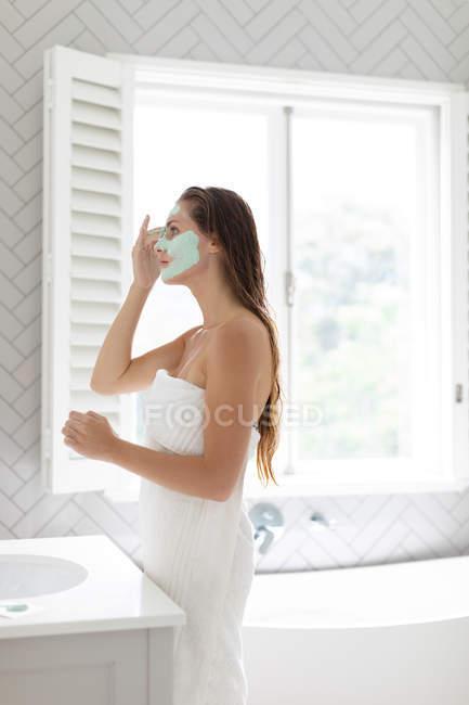 Seitenansicht einer Frau, die nach dem Bad eine Gesichtsmaske aufträgt — Stockfoto
