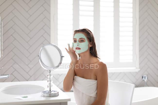 Frau schaut in den Spiegel und trägt Gesichtsmaske nach dem Bad im Badezimmer auf — Stockfoto