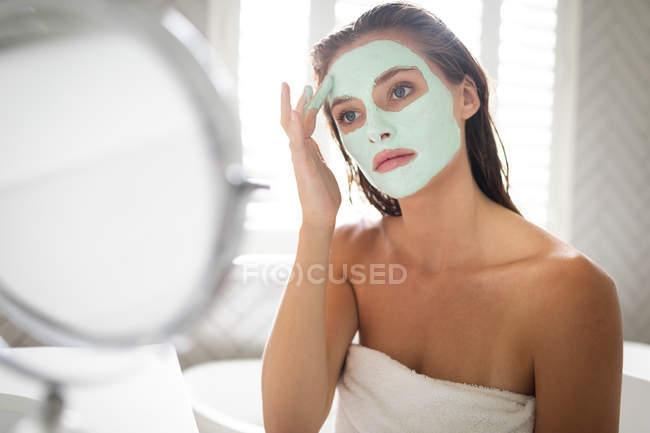 Nahaufnahme einer Frau, die nach dem Bad in den Spiegel schaut und eine Gesichtsmaske aufträgt — Stockfoto