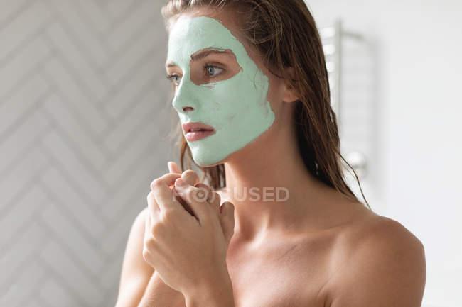 Nahaufnahme einer nachdenklichen Frau mit Gesichtsmaske im Badezimmer — Stockfoto