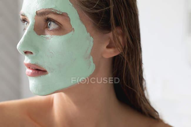 Nahaufnahme einer Frau mit Gesichtsmaske im Badezimmer — Stockfoto