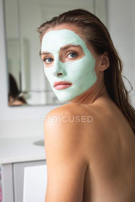 Nahaufnahme einer schönen Frau mit Gesichtsmaske im Badezimmer — Stockfoto