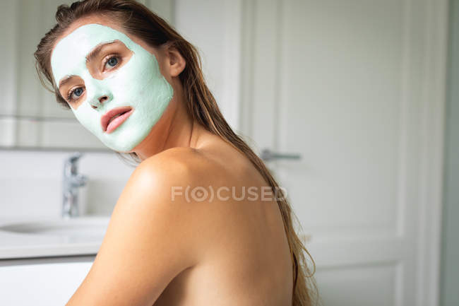 Close-up of beautiful woman in face mask looking at the camera — Stock Photo