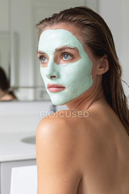 Gros plan de la femme en masque facial regardant loin dans la salle de bain — Photo de stock