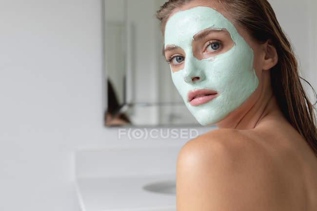 Gros plan femme en masque facial regardant la caméra dans la salle de bain — Photo de stock