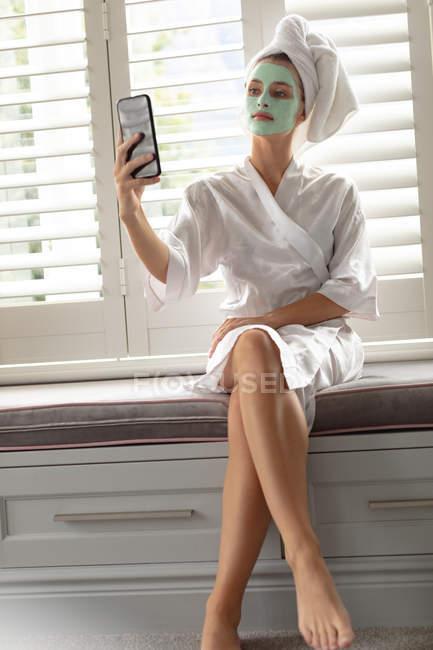 Schöne Frau im Bademantel macht ein Selfie zu Hause — Stockfoto