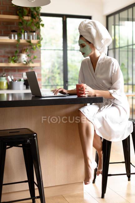 Жінка з чашкою кави використовує ноутбук на кухні після купання вранці. — стокове фото