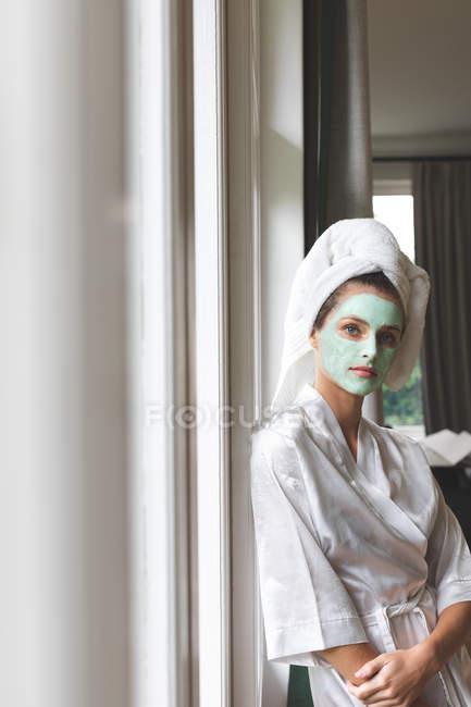 Schöne Frau im Bademantel mit Gesichtsmaske, gegen das Fenster gelehnt — Stockfoto
