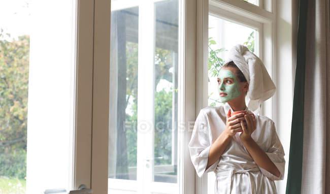 Schöne Frau im Bademantel mit Gesichtsmaske, die aus dem Fenster schaut — Stockfoto