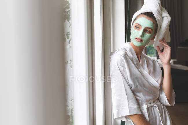 Beautiful woman in bathrobe wearing facial mask, looking through the window — Stock Photo