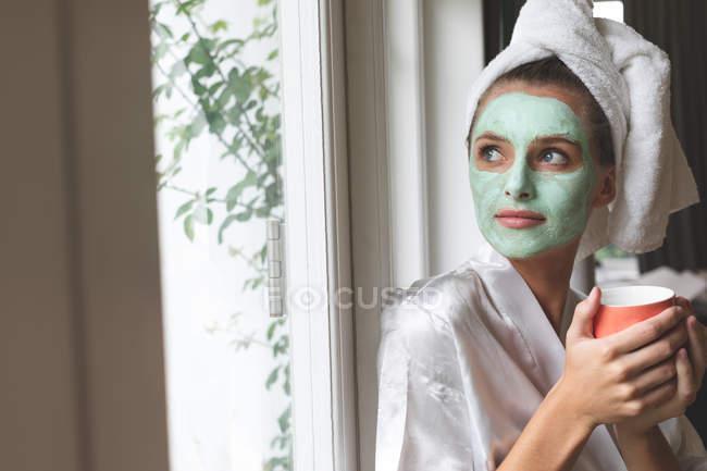 Bella donna in accappatoio indossando maschera facciale, guardando attraverso la finestra — Foto stock
