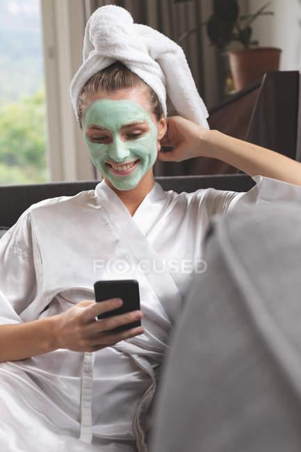 Vista frontale della donna in maschera facciale utilizzando il telefono cellulare sul divano a casa — Foto stock