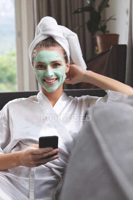 Frontansicht einer Frau mit Gesichtsmaske mit Handy auf dem heimischen Sofa — Stockfoto
