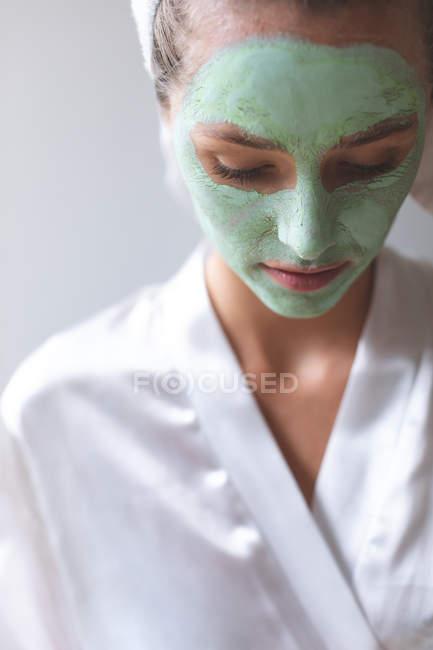 Frontansicht einer Frau mit Gesichtsmaske, die zu Hause nach unten schaut — Stockfoto