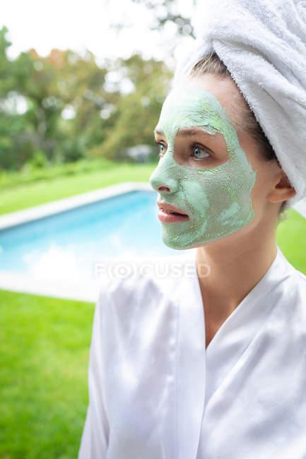Вид спереди женщины в маске, отводящей взгляд у бассейна — стоковое фото