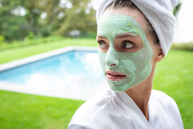 Front view of woman in face mask looking away near poolside — Stock Photo