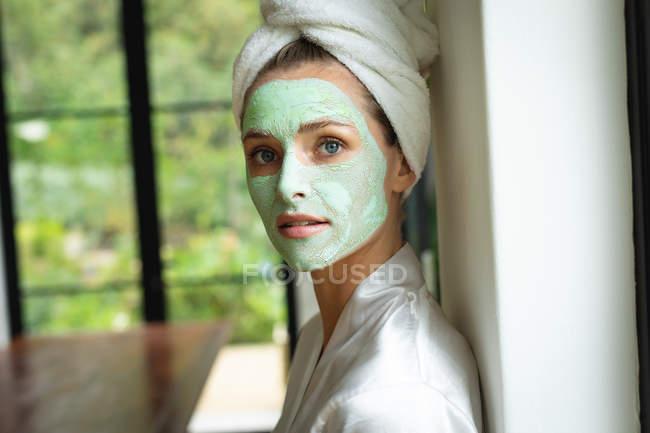 Портрет женщины в маске, смотрящей в камеру дома — стоковое фото